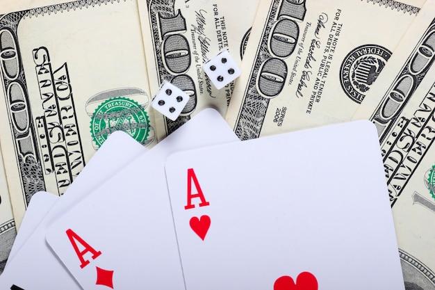 Asse von spielkarten mit würfeln und hundert-dollar-scheinen