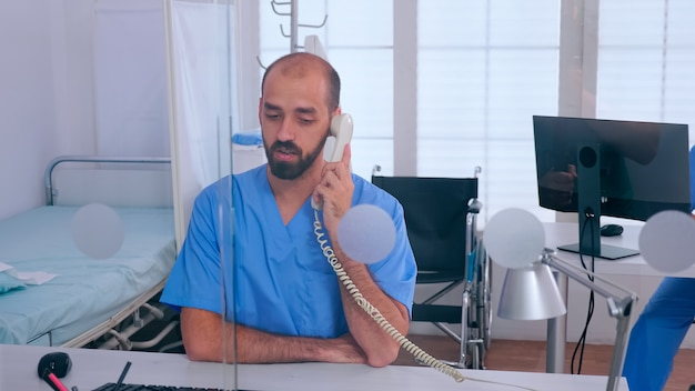 Assistent, der am telefon spricht, den termin überprüft, während die frau am pc arbeitet und im krankenhaus sitzt. arzt in der medizin einheitliche liste der konsultierten, diagnostizierten patienten, die forschung betreiben.