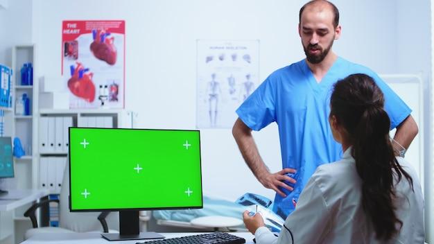 Assistent, der ein röntgenbild des arztes während der arbeit am computer mit grünem bildschirm im krankenhausschrank gibt. desktop mit austauschbarem bildschirm in der medizinischen klinik, während der arzt das röntgenbild des patienten überprüft