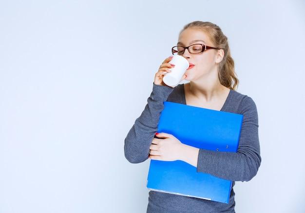 Assistent, der einen blauen ordner hält und eine tasse kaffee trinkt.