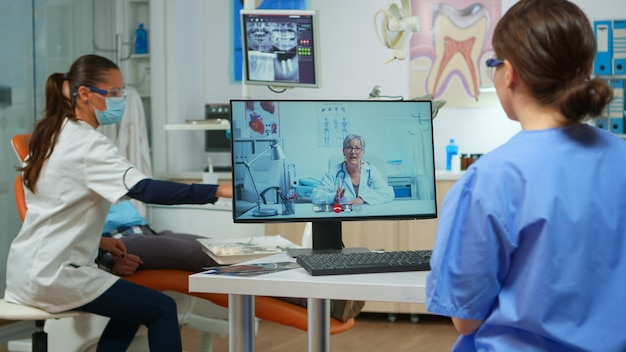 Assistent, der einen videoanruf mit einem erfahrenen stomatologischen arzt unter verwendung des computers hat, während der arzt mit dem patienten im hintergrund arbeitet. krankenschwester hört zahnarzt auf webcam auf stuhl im stomatologischen büro sitzend
