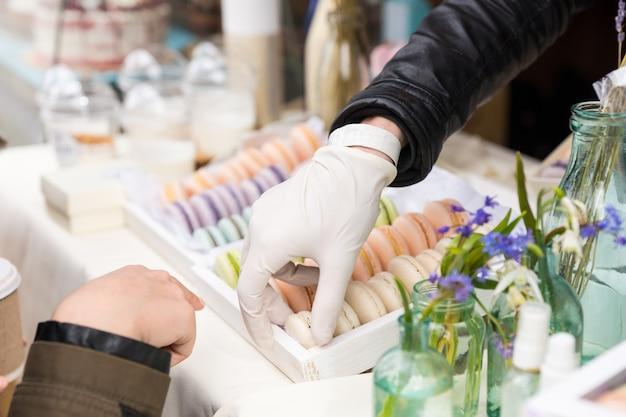 Assistent, der einer kundin einen französischen macaron oder eine makrone auf einem marktstand serviert, nahaufnahme auf ihren händen und dem tablett mit keksen