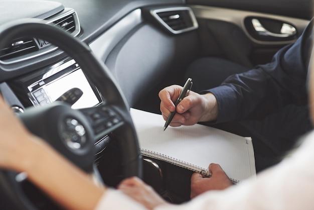 Assistent des managers, der dem kunden im autosalon ratschläge und hilfe gibt