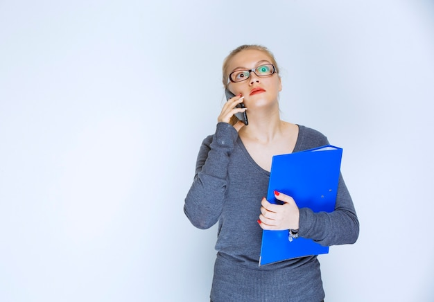 Assistent mit brille hält einen blauen ordner und spricht mit dem telefon.