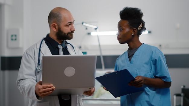 Assistent mit schwarzer haut und praktischer arzt in medizinischer uniform, der krankheitssymptome überwacht