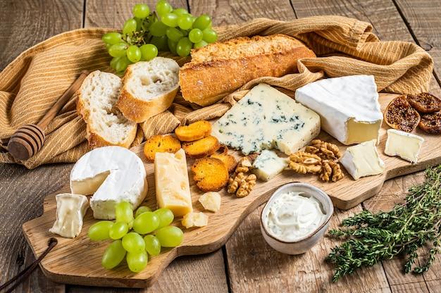 Assorted cheese brie, camembert, roquefort, parmesan, blauschimmelkäse mit trauben, feigen, brot und nüssen. hölzerner hintergrund. ansicht von oben.