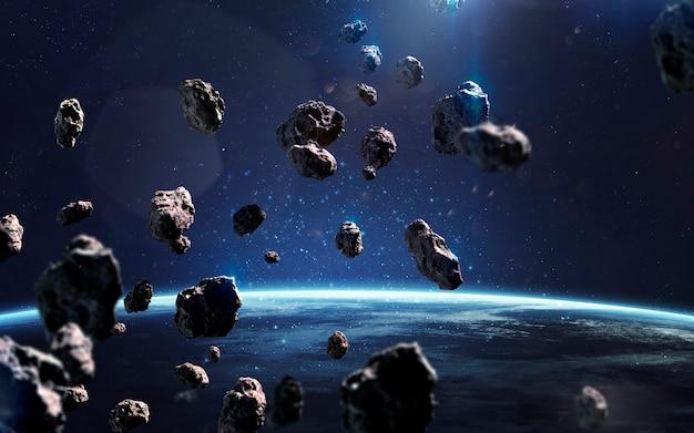 Asteroiden in der nähe der erde. meteoriten umkreisen den planeten. deep space image, science-fiction-fantasie in hoher auflösung, ideal für tapeten und drucke. elemente dieses bildes von der nasa geliefert