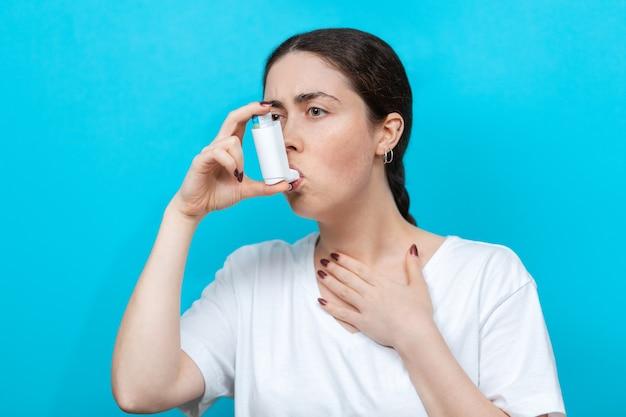 Asthma. porträt einer jungen frau mit einem inhalator. blauer hintergrund.