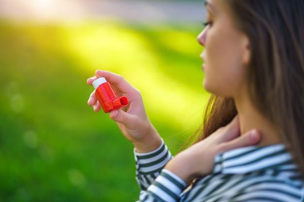 Asthmatiker leiden an erstickung und verwenden inhalator von einem asthmaanfall im freien