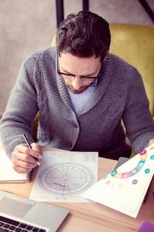 Astrologisches schema draufsicht eines gutaussehenden intelligenten mannes, der die zeichnung betrachtet, während eine vorhersage macht