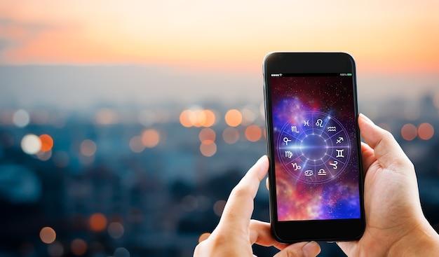 Astrologisches tierkreishoroskop mobiles anwendungskonzeptmannhände, die handy halten