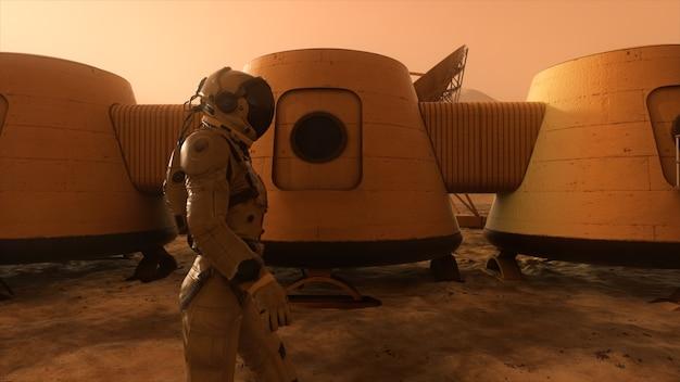 Astronaut auf dem planeten mars, der einen umweg um seine basis macht. astronaut, der entlang der basis geht.