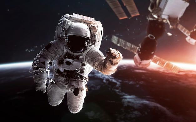 Astronaut auf der erdumlaufbahn mit der raumstation dahinter.