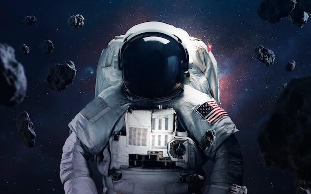 Astronaut, der an den fantastischen kosmischen hintergründen mit glühenden sternen und asteroiden spaziert