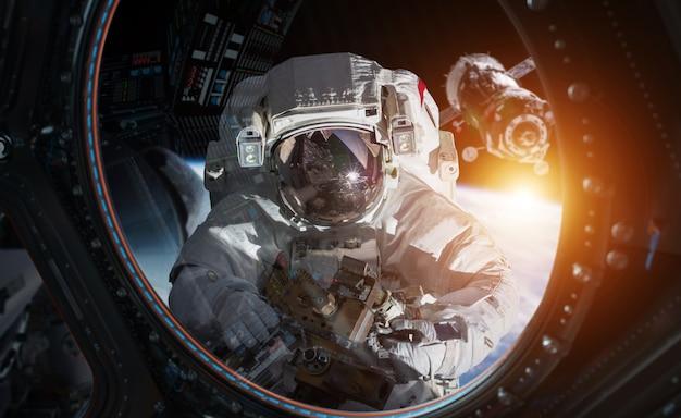 Astronaut, der an einer wiedergabe der raumstation 3d arbeitet