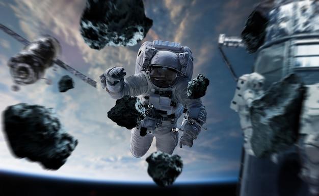 Astronaut, der an wiedergabeelementen einer raumstation 3d arbeitet