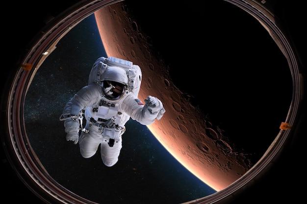 Astronaut im weltraum vom bullauge auf dem hintergrund des mars
