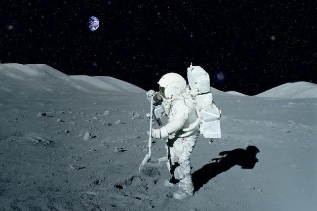 Astronaut in der nähe des mondrovers auf dem mond. mit land am horizont. elemente dieses bildes wurden von der nasa bereitgestellt. für jeden zweck.