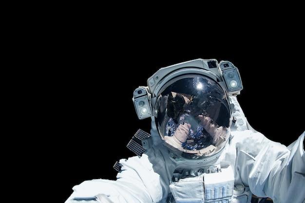 Astronaut in einem raumanzug auf schwarzem hintergrund isoliert. elemente dieses bildes wurden von der nasa bereitgestellt. foto in hoher qualität