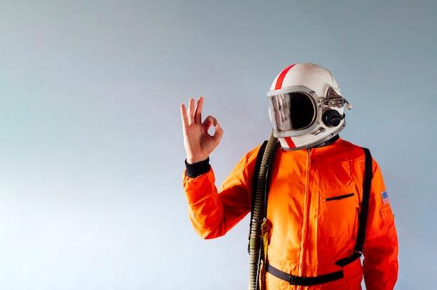 Astronaut mann mit ok-symbol auf grauem hintergrund. platz kopieren