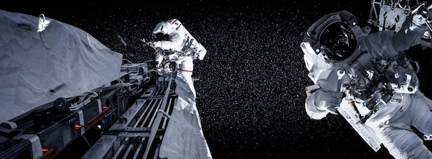 Astronauten-raumfahrer machen einen weltraumspaziergang, während sie für eine raumstation arbeiten
