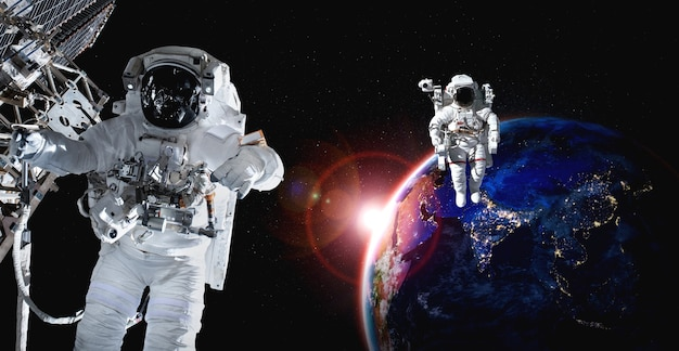 Astronauten-raumfahrer machen weltraumspaziergang, während sie für die raumstation arbeiten working