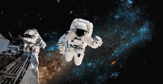 Astronauten-raumfahrer machen weltraumspaziergang, während sie für die raumstation arbeiten