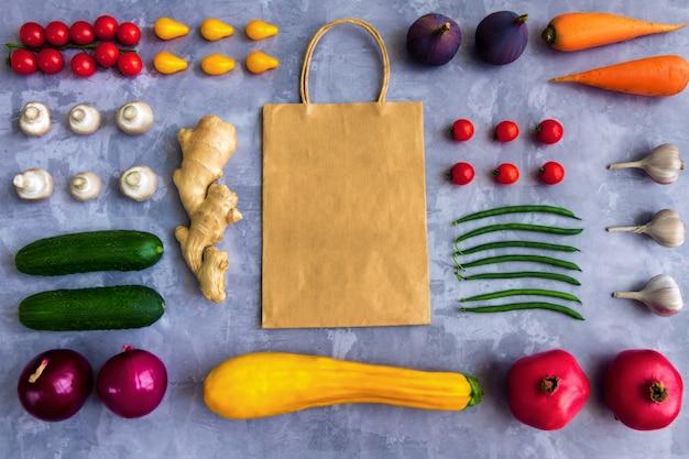 Asty frisches sommer rohes organisches antioxidans buntes obst- und gemüsegemüse: karotte, tomate, knoblauch, zwiebel, ingwer lokalisiert auf hintergrund mit papierpaket. veganes und vegetarisches lebensmittelkonzept
