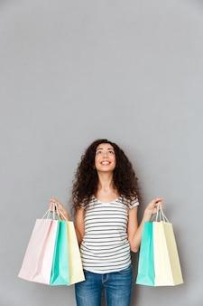 Atelieraufnahme der lächelnden frau vergnügen und glück ausdrückend, nachdem viele waren oder geschenke im einkaufszentrum gekauft worden sind, das oben mit dankbarkeit schaut