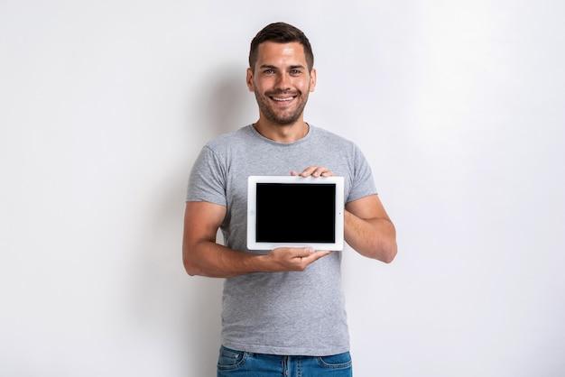Atelieraufnahme des glücklichen mannes ein ipad mit schwarzem leerem leerem bildschirm halten.