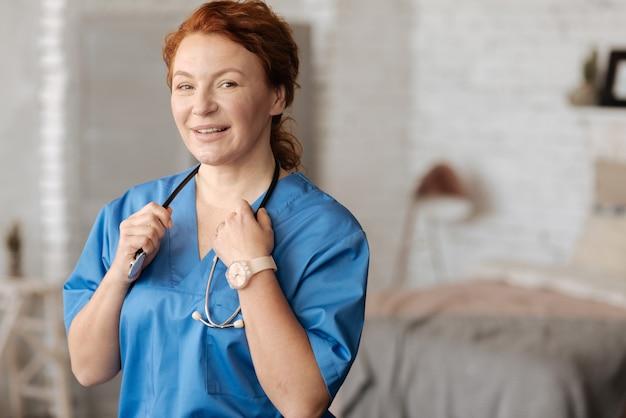 Atemberaubend und qualifiziert. motivierte charismatische sanfte frau, die zu hause medizinische leistungen erbringt, während sie professionelle ausrüstung verwendet und eine spezielle uniform trägt