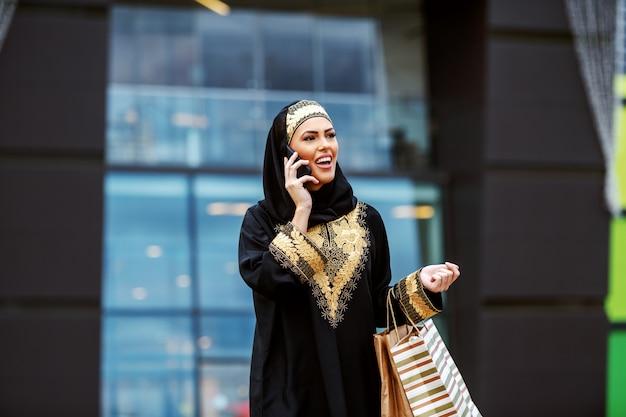 Atemberaubende attraktive positiv lächelnde muslimische frau in traditioneller kleidung, die vor dem einkaufszentrum mit einkaufstüten in den händen steht und taxi ruft.