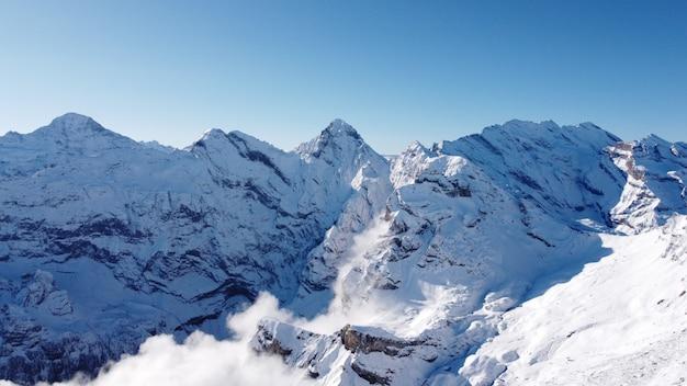Atemberaubende aufnahme des gipfels der schneebedeckten alpen, die von wolken bedeckt sind