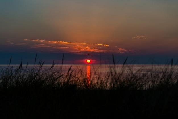 Atemberaubende aufnahme des sonnenuntergangs über dem ozeanufer bei vrouwenpolder, zeeland, die niederlande