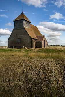 Atemberaubende aufnahme einer alten kirche und grasfläche in großbritannien an einem wolkigen tag
