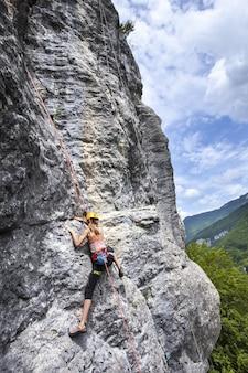 Atemberaubende aufnahme einer frau, die auf dem hohen felsen in champfromier, frankreich, klettert