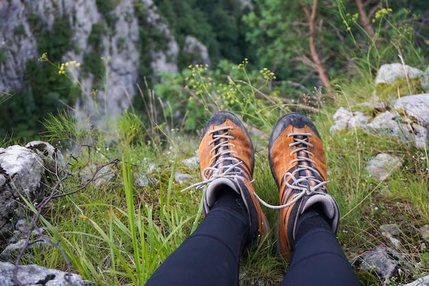 Atemberaubende aufnahme einer person, die auf einem gelände von grasfelsen und blumen in einem campingplatz sitzt