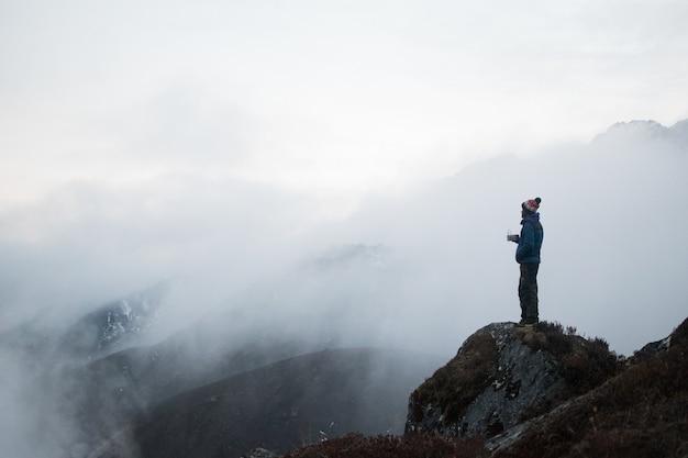 Atemberaubende aufnahme eines mannes, der auf einem großen felsen steht, umgeben von nebligen bergen