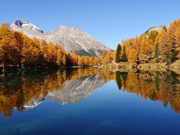 Atemberaubende aufnahme eines reflektierenden sees auf einer berglandschaftsoberfläche