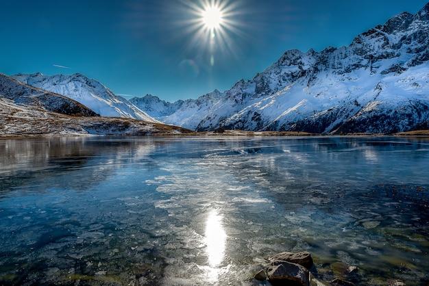 Atemberaubende aufnahme eines schönen gefrorenen sees, umgeben von schneebedeckten bergen während eines sonnigen tages
