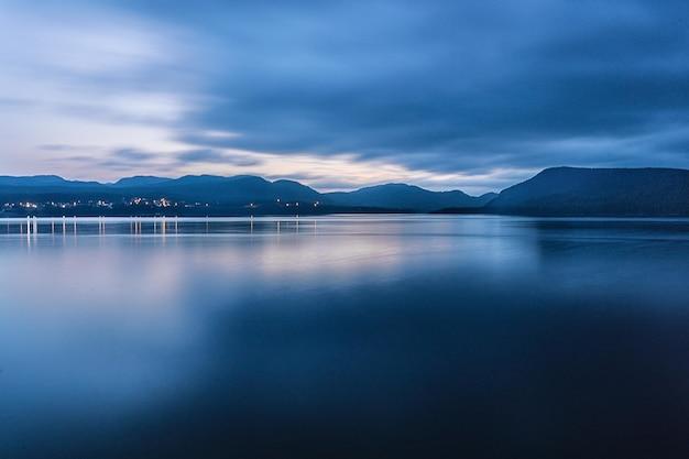 Atemberaubende aufnahme eines tiefblauen ozeans und einer bergkette an einem dunklen und wolkigen tag