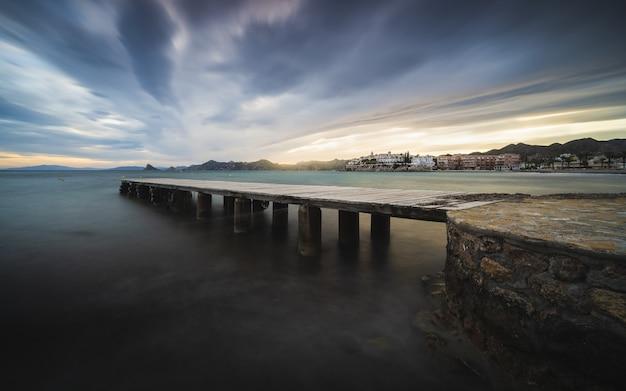 Atemberaubende aussicht auf die seelandschaft mit einem hölzernen pier am malerischen dramatischen sonnenuntergang
