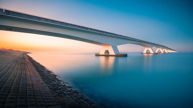 Atemberaubende aussicht auf eine brücke über einen friedlichen fluss in zeelandbridge, niederlande