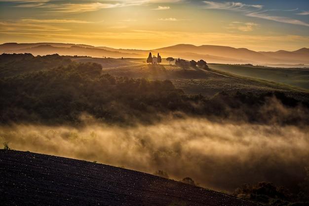 Atemberaubende aussicht auf grüne hügel, umgeben von nebel mit einem gebäude in der ferne