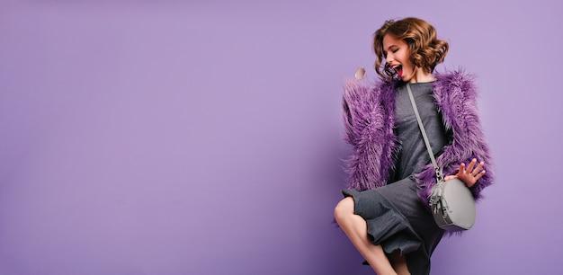 Atemberaubende barfüßige frau im trendigen pelzmantel, die auf fotoshooting tanzt und lacht