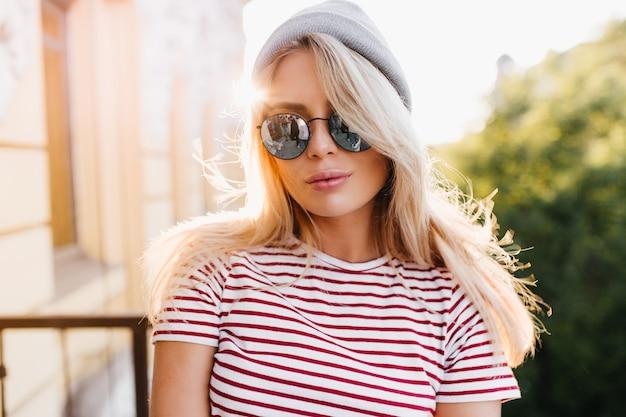Atemberaubende blonde frau in der sommerkleidung posiert auf dem balkon und genießt das sonnenlicht am frühen abend