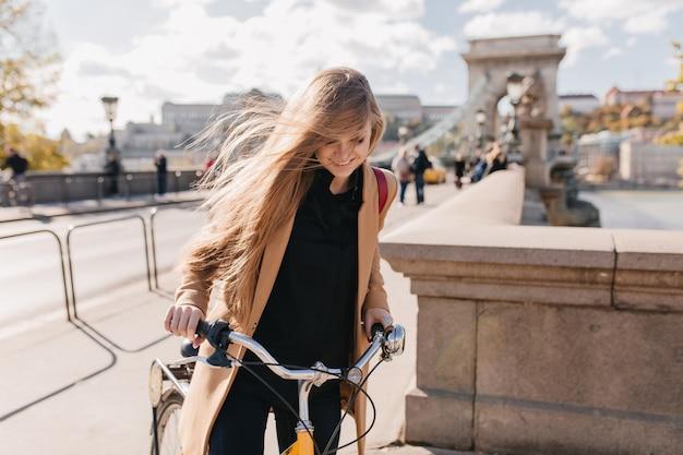Atemberaubende blonde frau mit glattem haar, die fahrrad durch stadt fährt