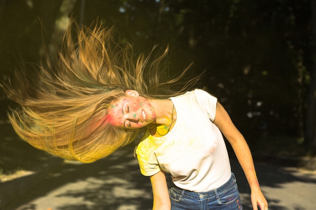 Atemberaubende blonde frau mit wind im haar und leuchtenden farben, die um sie herum explodieren