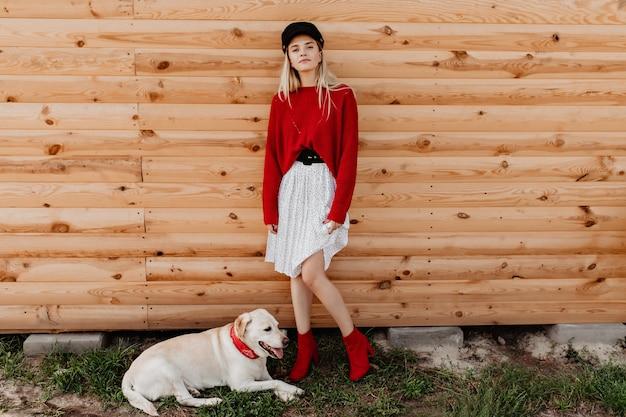 Atemberaubende blondine im weißen rock und im roten pullover, der auf der holzwand aufwirft. schönes mädchen, das sich ruhig und gut mit ihrem hund im freien fühlt.