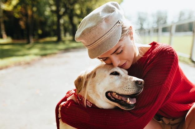 Atemberaubende blondine mit ihrem geliebten hund, der im herbst zeit miteinander im freien verbringt. schönes porträt einer jungen frau und ihres haustieres im park.